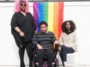 The Margins: Three Black and disabled folx (a non-binary person holding a cane, a woman sitting in a power wheelchair, and a woman sitting in a chair) looking seriously at the camera while a rainbow pride flag drapes on the wall behind them. Credit: Disabled and Here