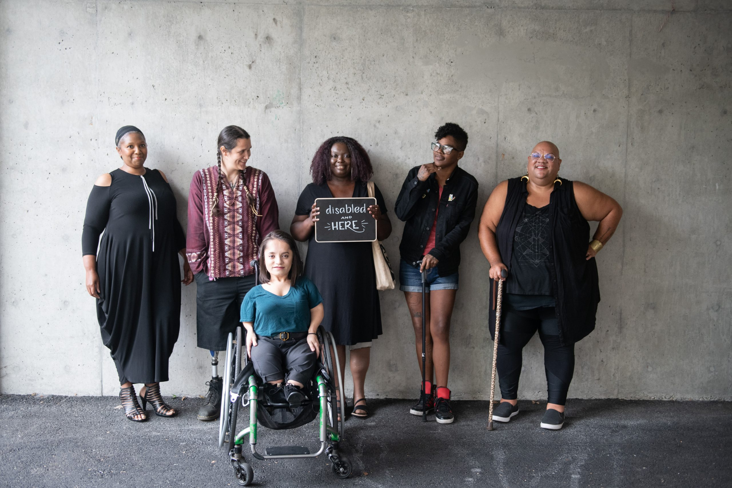Line up of six disabled people showing disability pride